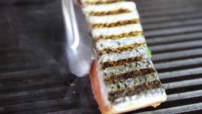 Le cuisinier prépare saumoné sur le gril clips vidéos