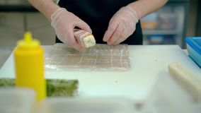 Le cuisinier prépare un petit pain japonais avec du riz et le lard clips vidéos