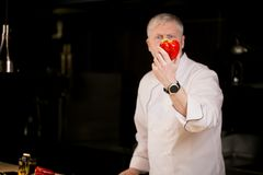 Le cuisinier principal tient le poivron rouge sur son bras Photos libres de droits