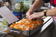 Le cuisinier prépare une cocotte en terre Image stock