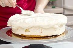 Le cuisinier répand la crème sur le gâteau Image stock