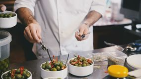 Le cuisinier répand les cuillères dans des cuvettes banque de vidéos