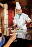 Le cuisinier sert le plat à un client Photographie stock libre de droits