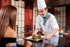 Le cuisinier sert le plat à un client Photo stock