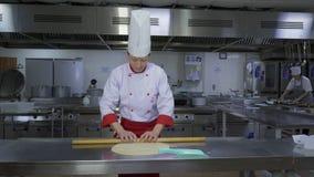 Le cuisinier sur la table de coupe déroule la pâte clips vidéos