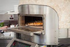 le cuisinier tire la pizza cuite au four par lave images stock