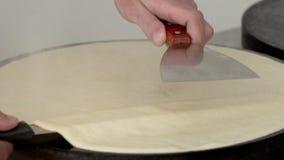 Le cuisinier tourne une crêpe sur une surface professionnelle dans le mouvement lent clips vidéos