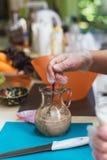 Le cuisinier verse l'eau bouillante au-dessus de la levure pour obtenir la mâche pour la pâte Faisant la pâte en diluant la levur images libres de droits