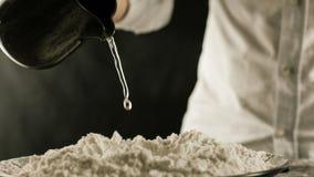Le cuisinier verse l'eau sur la farine de la cruche dans la cuisine photos stock