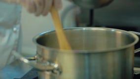 Le cuisinier verse la farine pour faire la p?te dans une casserole, puis la m?lange ? une spatule banque de vidéos