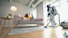 Le cyborg blanc nettoie une maison tandis qu'une femme parle à un téléphone banque de vidéos