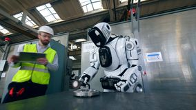 Le cyborg traite le métal avec un travailleur presque se tenant banque de vidéos