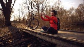 Le cycliste caucasien heureux de femme fait ? une photo d'elle-m?me un selfie au t?l?phone tout en se reposant sur le pont au-des images stock