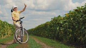 Le cycliste de femme attrape un signal de téléphone en nature banque de vidéos