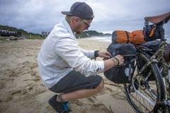 Le cycliste de fond prépare des sacoches tandis que sur la plage image stock