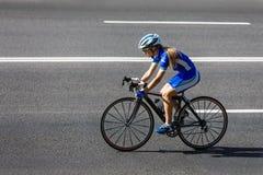 Le cycliste féminin monte un vélo de emballage sur la route Photographie stock