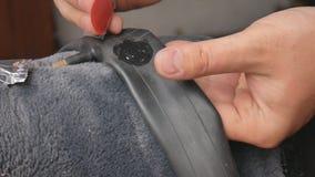 Le cycliste ou le mécanicien applique la colle sur la chambre à air perforée Fermez-vous des mains et du pneu de pneu crev? de bi banque de vidéos
