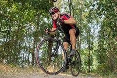 Le cycliste sur un vélo de route monte dans le terrain Images libres de droits