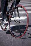 Le cycliste sur le vélo de route traverse la voie urbaine avec les hôtes piétonniers Image stock