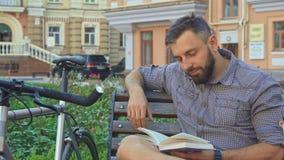 Le cycliste tourne la page du livre sur le banc photos libres de droits