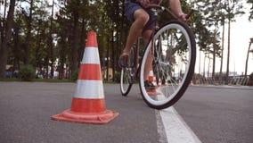 Le cycliste vont autour des cônes du trafic Jeune homme bel montant une bicyclette de vintage Type sportif faisant un cycle au pa photographie stock libre de droits