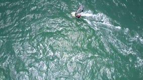 Le débutant de surfer avec la voile transparente s'exerce sur les vagues lourdes banque de vidéos
