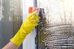 Le décapant avec une éponge lave la fenêtre Photo libre de droits