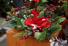 Le décor de nouvelle année dans un panier des branches coniféres vertes, des feuilles rouges et des baies sous la neige blanche s photo stock