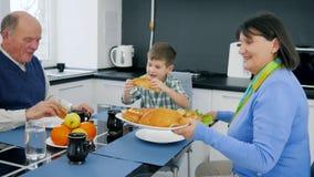 Le déjeuner de famille de retraité, dame âgée a apporté le pain délicieux du plat pour les petits-enfants et le grand-papa s'asse banque de vidéos