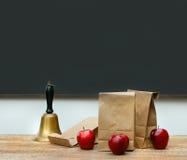 Le déjeuner met en sac avec les pommes et la cloche d'école sur le bureau Photos libres de droits