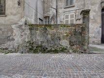 Le délabrement antique de mousse de mur se décomposent derrière le pavior de pavé rond Photos libres de droits
