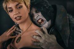 Le démon antique de vampire de monstre mord un cou de femme Halloween fant Image stock