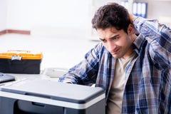 Le dépanneur de matériel réparant le télécopieur cassé d'imprimante photo stock