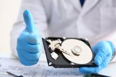 Le dépanneur masculin portant les gants bleus tient l'unité de disque dur Photographie stock