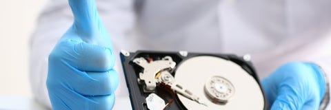 Le dépanneur masculin portant les gants bleus tient l'unité de disque dur Image libre de droits