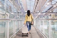 Le déplacement asiatique de voyageuse de femme continuent la valise de bagage au couloir d'aéroport marchant aux portes de départ Photographie stock libre de droits