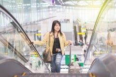 Le déplacement asiatique de voyageuse de femme continuent la valise de bagage au couloir d'aéroport marchant aux portes de départ Images stock