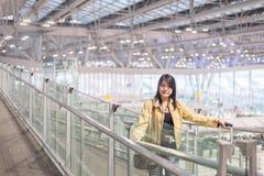 Le déplacement asiatique de voyageuse de femme continuent la valise de bagage au couloir d'aéroport marchant aux portes de départ Photographie stock