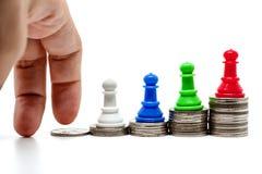 Le déplacement de doigts intensifient l'escalier de pièces de monnaie avec le gage d'échecs dessus à Photographie stock