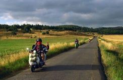 Le déplacement le long de la route dans les montagnes des cyclistes sur de vieux vélos montrant la victoire signent Photos stock