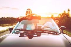 Le déplacement par les couples automobiles dans l'amour vont en voiture de cabriolet dans le coucher du soleil Photographie stock libre de droits