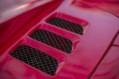 Le détail de la voiture rouge de superbe-sport exhale sur un capot image stock