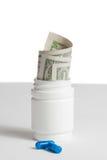 Le détail des pilules bleues devant le récipient avec l'intérieur a roulé vers le haut des dollars sur le fond blanc Photos stock