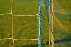 Le détail du bleu jaune a croisé les filets du football, le football du football dans le filet de but avec la pauvre herbe sur le Photographie stock libre de droits