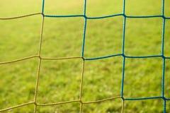 Le détail du bleu jaune a croisé les filets du football, le football du football dans le filet de but avec la pauvre herbe sur le Images libres de droits
