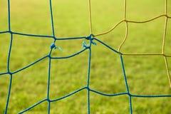 Le détail du bleu jaune a croisé les filets du football, le football du football dans le filet de but avec la pauvre herbe sur le Images stock