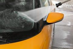 Le détail sur la fenêtre avant de voiture jaune foncée et le miroir arrière étant était image stock