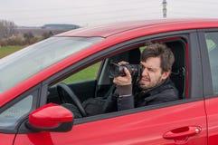 Le détective prend la photo avec l'appareil-photo de la voiture Photos stock