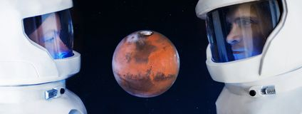 Le développement de Mars, concept Deux astronautes, un homme et femme regardant la planète Mars Photos stock