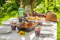 Le dîner d'été avec des pommes de terre et le poulet ont servi dans le jardin Photo libre de droits